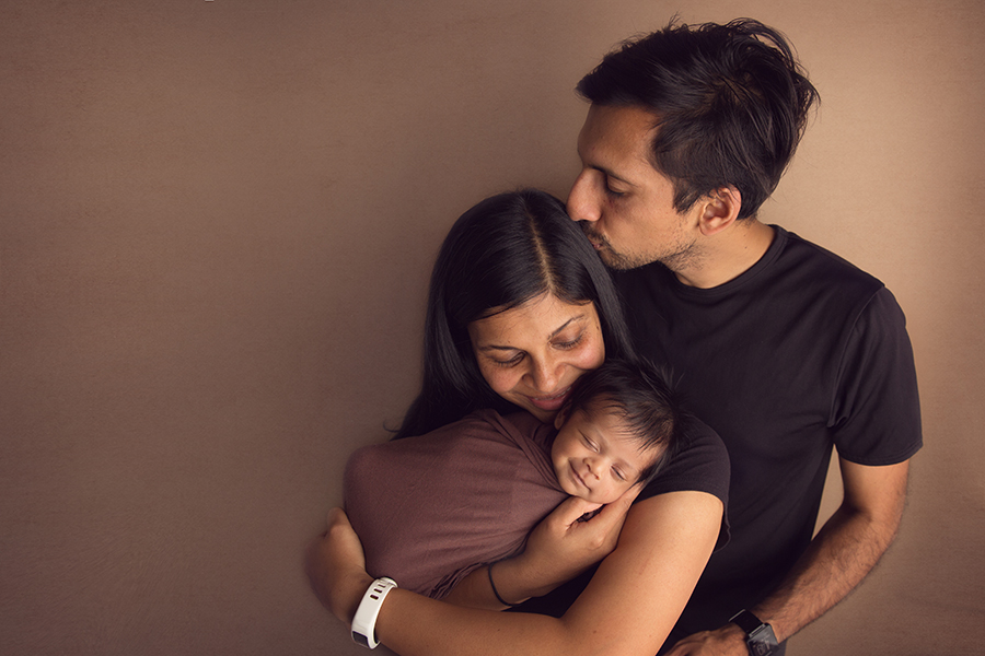 Family photo of parents with their newborn baby boy who is smiling on a warm brown backdrop