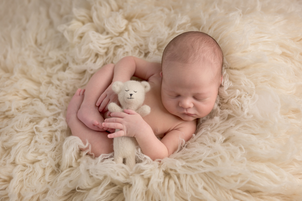 Newborn baby lying on a cream float rug cuddling a cream teddy