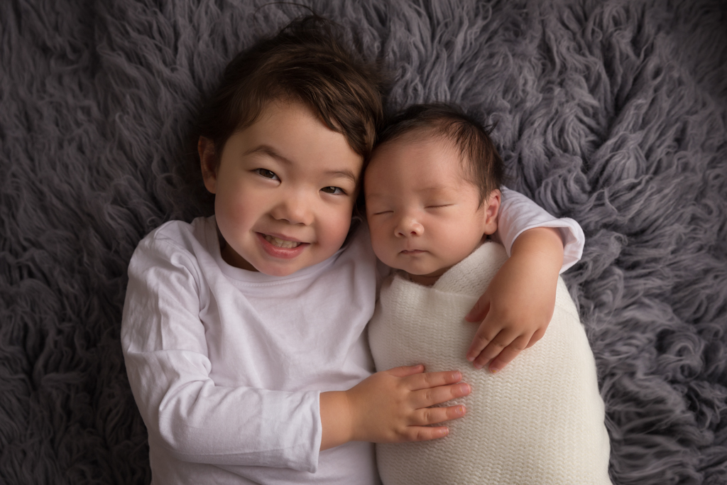 Sibling photograph of three year old girl with her new baby brother cuddling him on a grey wrap