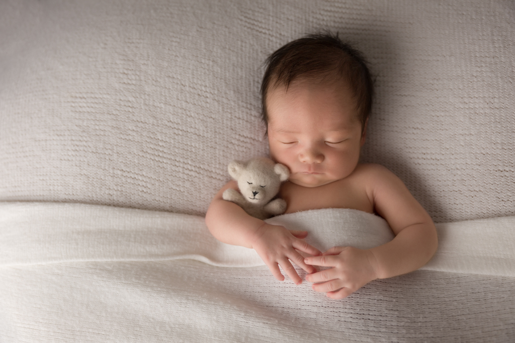 Sleepy time pose for newborn baby cuddling teddy on a whit blanket