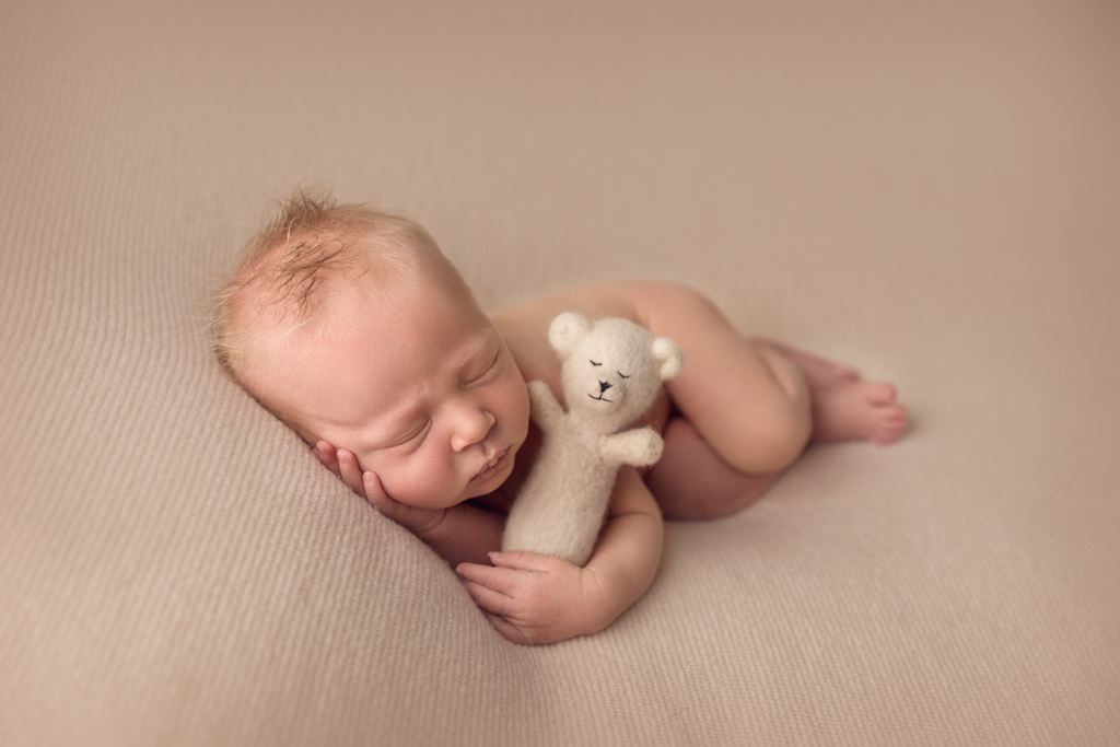 Newborn photograph of baby boy on cream blanket lying on his side with teddy