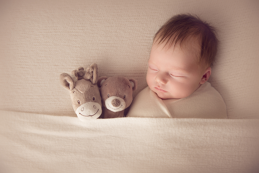 Newborn in sleepy time pose with two teddies as his friend