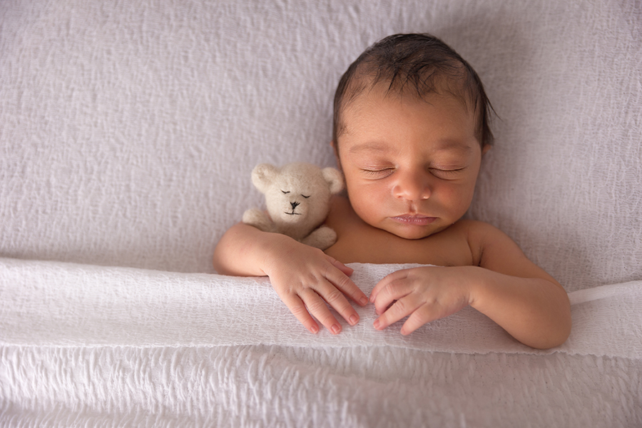 Sleeping baby with teddy in a white bed