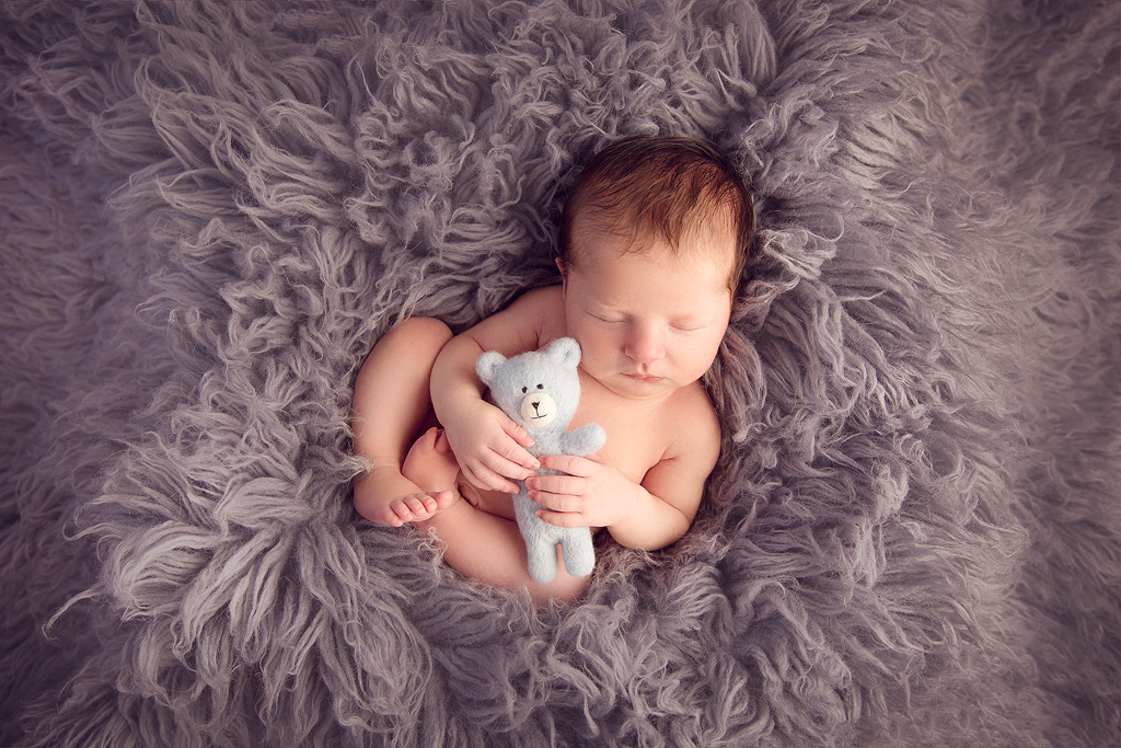 Baby lying on grey flokati holding little teddy bear