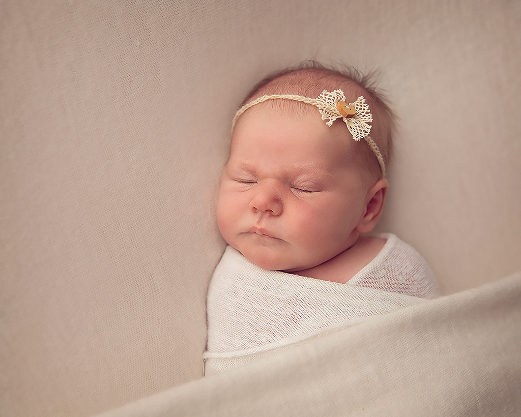 Baby girl wrapped up asleep wearing cream headband