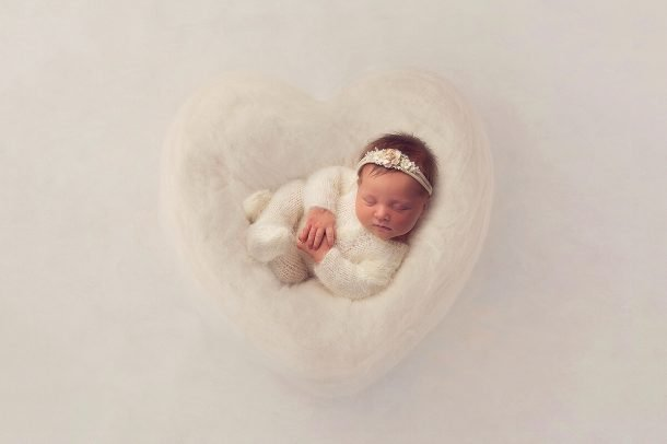 newborn baby in white romper lying in a white heart