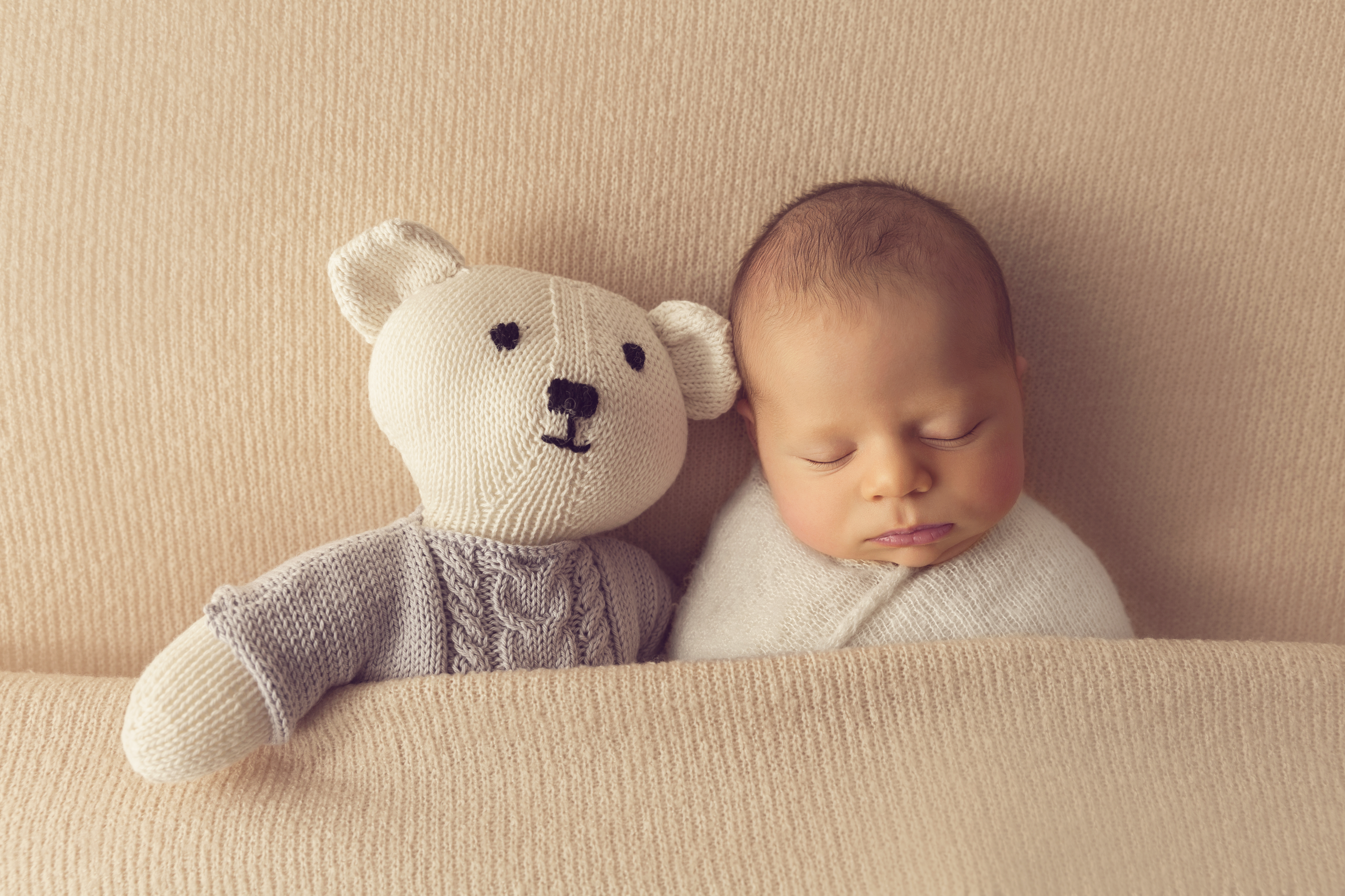 newborn photographed on cream blanket with teddy